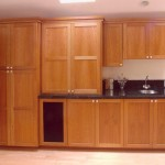 a bank of wood cabinets with a black granite countertop