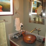 A remodeled bathroom vanity with a raised glass bowl
