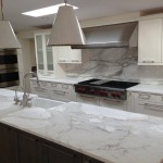 A remodeled kitchen with a slab of granite island matching backsplash