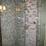 A remodeled shower with slate grey tiling and glass doors.