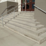 An outdoor stone staircase with a center railing
