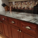 A side profile of a grey marbled granite countertop with cherry wood cabinets