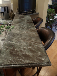 A granite bar are with bar stools.