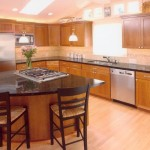An example of a fully remodeled kitchen with island with black granite countertops and dark natural wood cabintes.