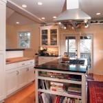 A remodeled kitchen with a black granite island.