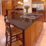A remodeled kitchen with a black island countertop with stove top shaped like a wedge.