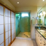 A remodeled bathroom with a green granite countertop and two sinks.