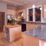 A new kitchen with grey granite countertops, light natural wood cabinets, and a hardwood floor.