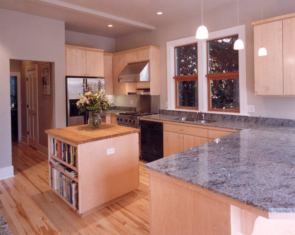 A New Kitchen With Grey Granite Countertops, Light Natural Wood Cabinets,  And A Hardwood