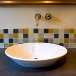 An example photo of a white bathroom sink bowl with various green tile backsplash.